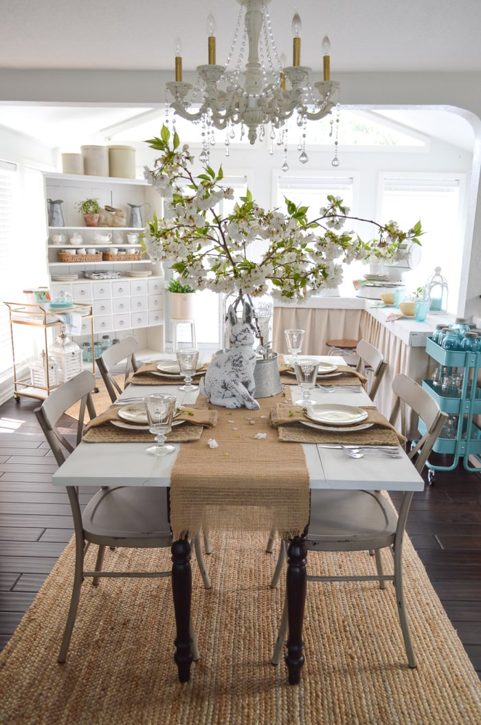 Easter tablescape with burlap runners, white flowers and white dishes