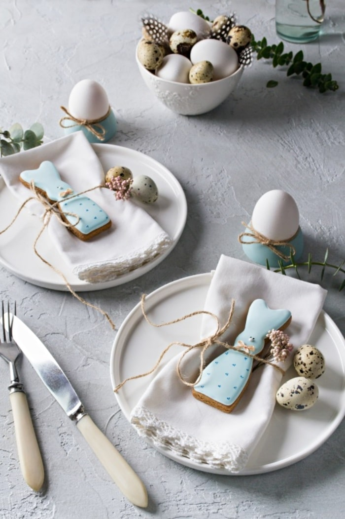 Easter table setting with white dishes and napkins and blue bunny cookies