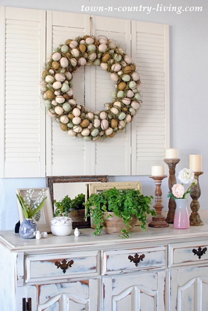 Easter egg wreath hanging on white shutters above a sideboard with spring decor
