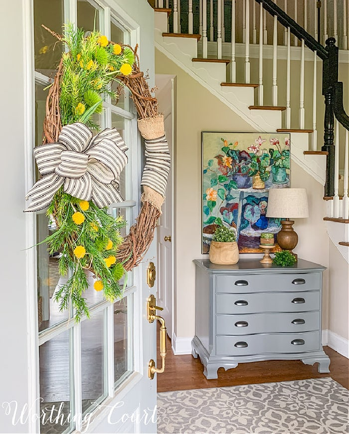 view looking through front door with a wreath into a foyer with a grey chest topped with colorful artwork
