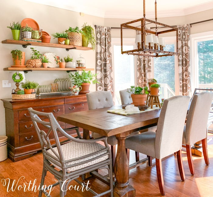 dining area with table, chairs. sideboard and open shelves decorated with terra cotta