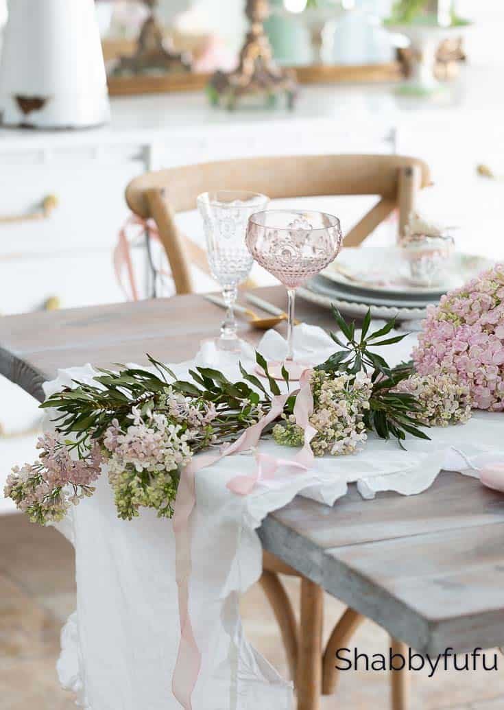 one end of a spring garland down the center of the table with white and pink flowers