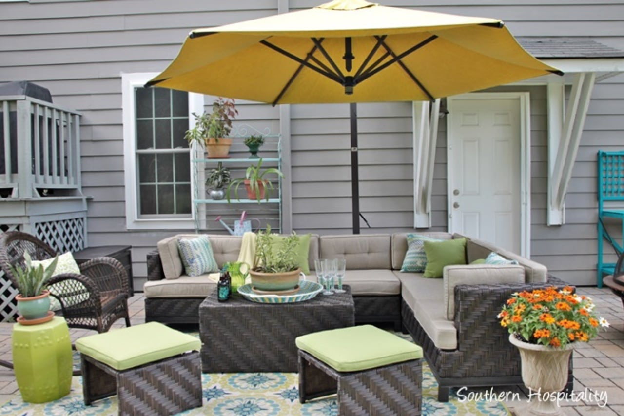 outdoor furniture on a patio with an umbrella and flowers