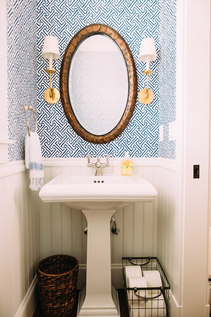 pedestal sink with blue and white wallpaper, an oval mirror and gold wall sconces