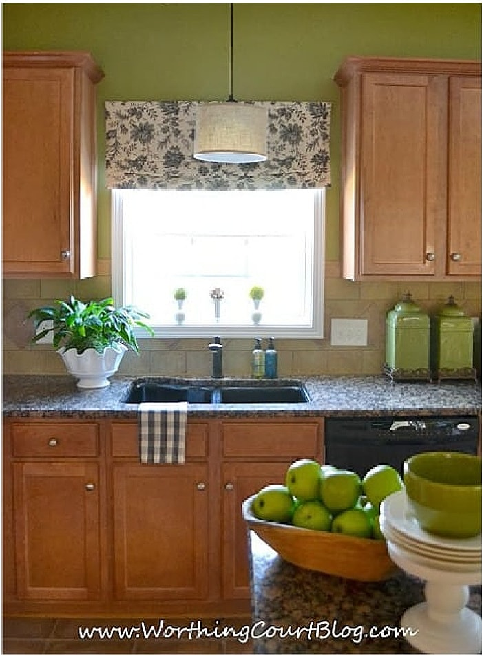 kitchen with maple cabinets, window over a sink and green walls