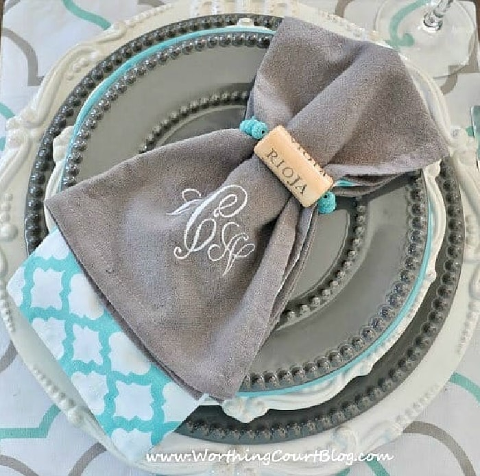 stack of gray and white plates with blue, white and gray napkin and a diy wine cork napkin ring