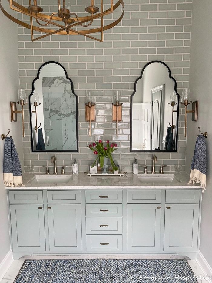 bathroom with gray tiled walls, matching pair of mirrors and a painted gray vanity