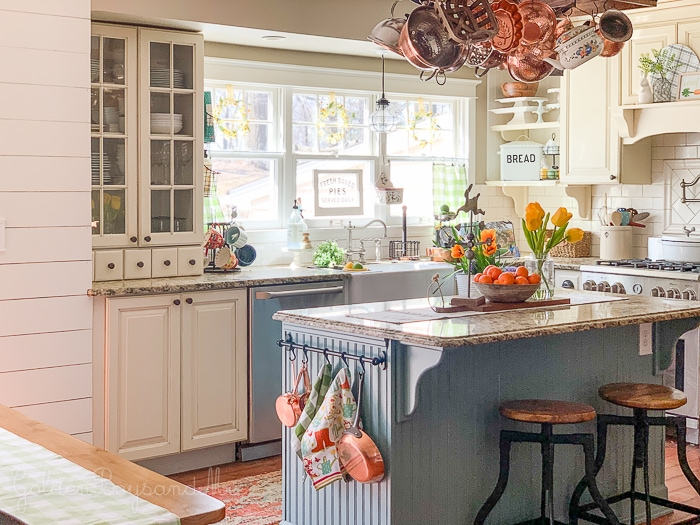 kitchen with white cabinets and blue island with copper pots