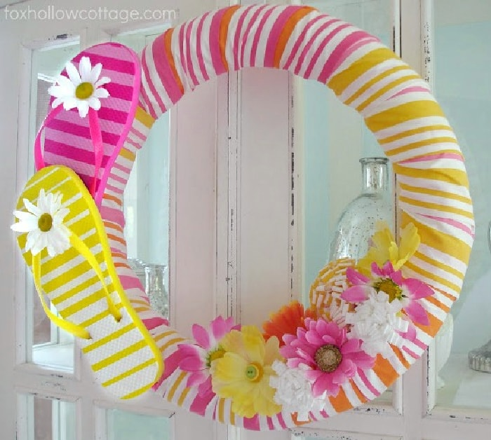yellow, orange, white and pink wreath made with flip flops and summer flowers