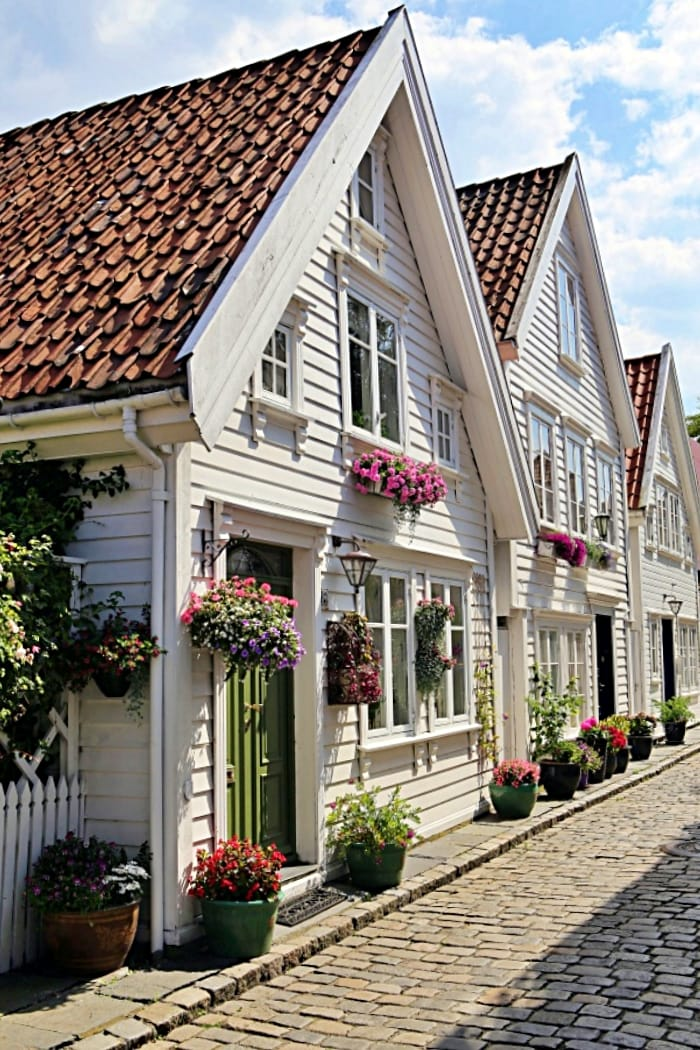 house with white siding and pink flowers in planters