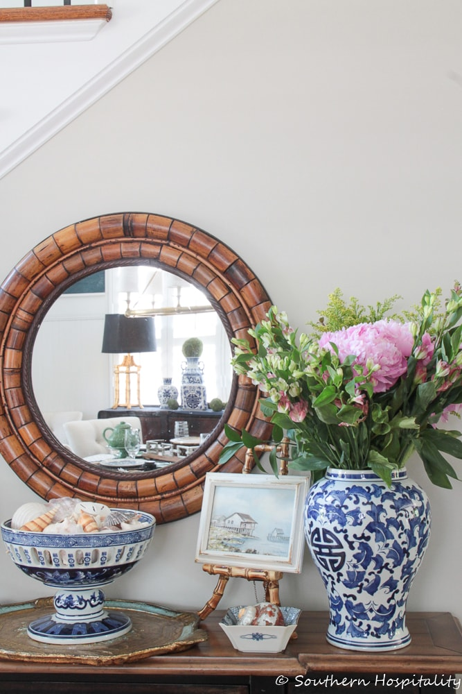 vignette with blue and white accessories and a round mirror on a console table