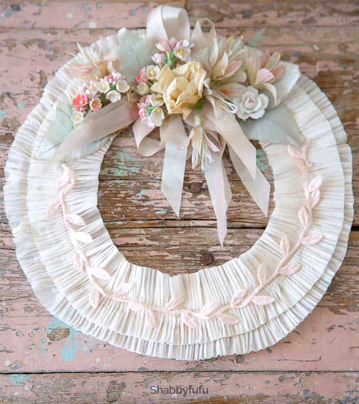 white wreath with faux flowers and ribbon
