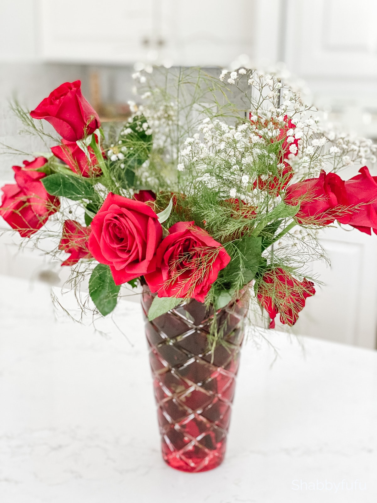 red roses in a red quilted vase