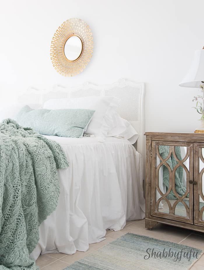white bedspread on a bed with blue throw pillows and a blue blanket throw