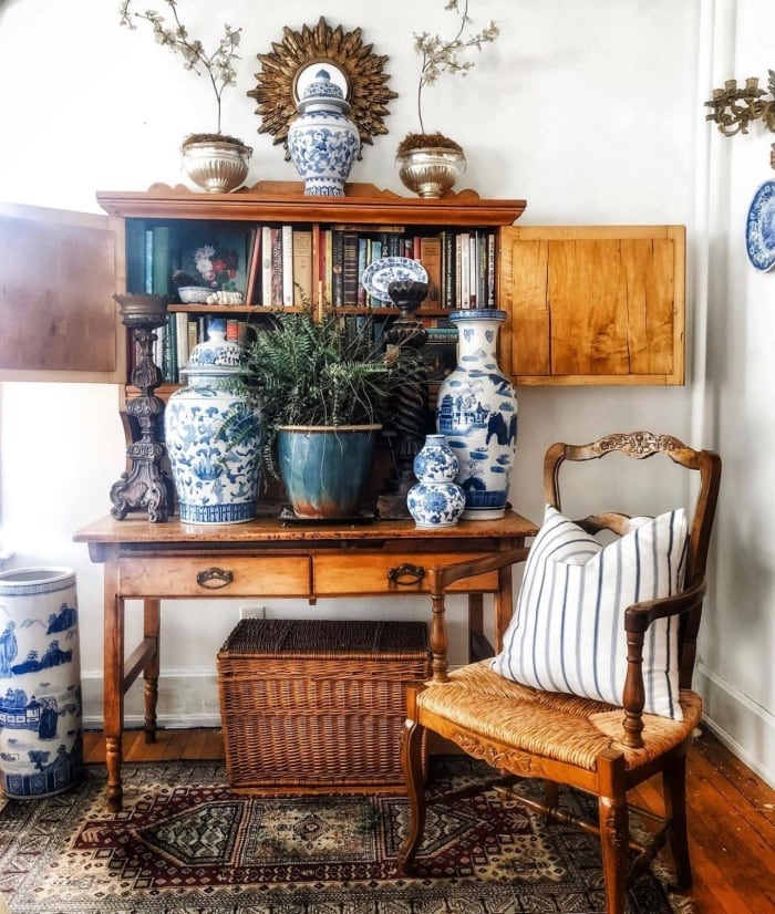 antique secretary desk filled with books and blue and white accessories