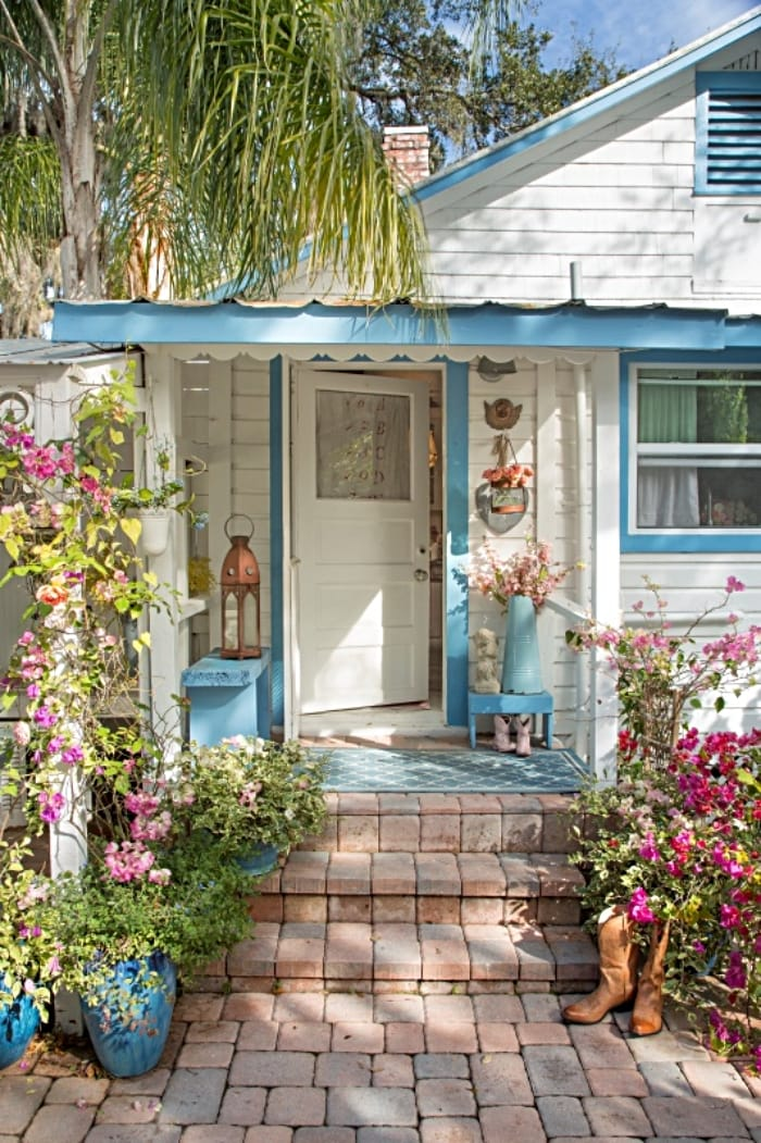 cottage painted white with blue trim and pink roses