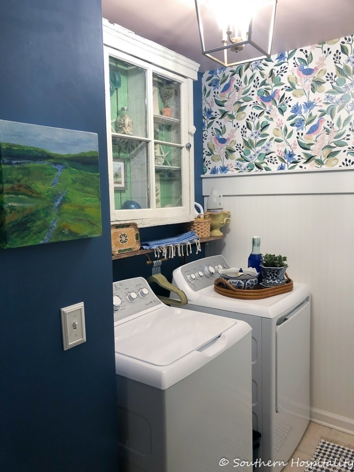 laundry room with blue wall and a floral wallpaper wall