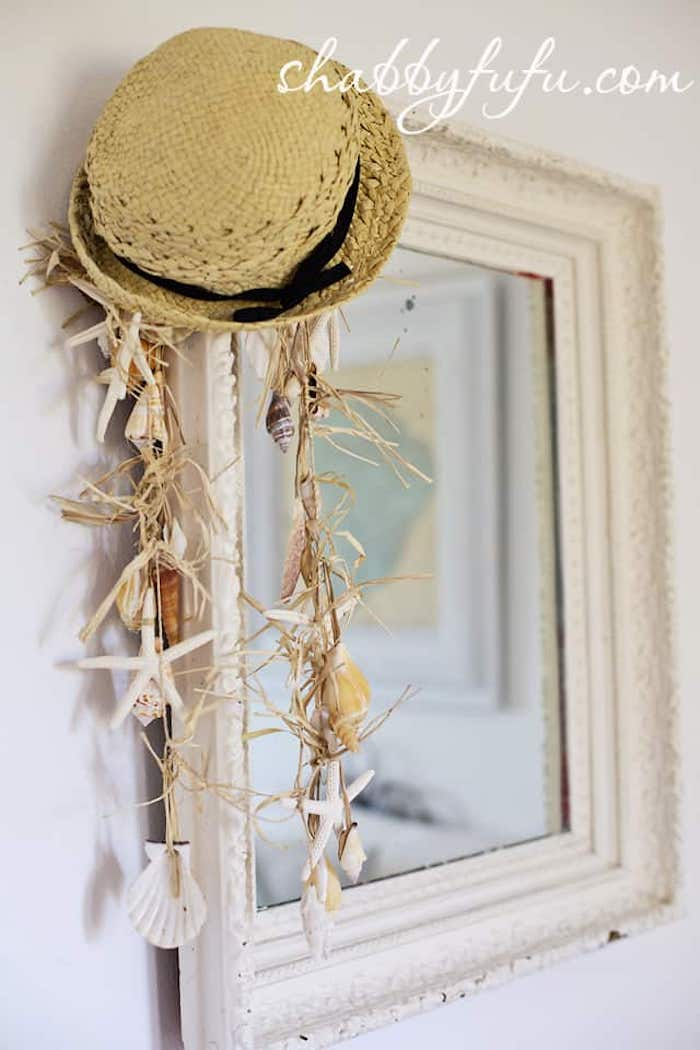 mirror with white frame with a straw hat and shell garland hanging from corner