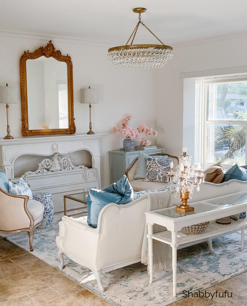transitional interior design style living room with rugs and pillows in blue shades, white sofas, golden mirrors and lights.