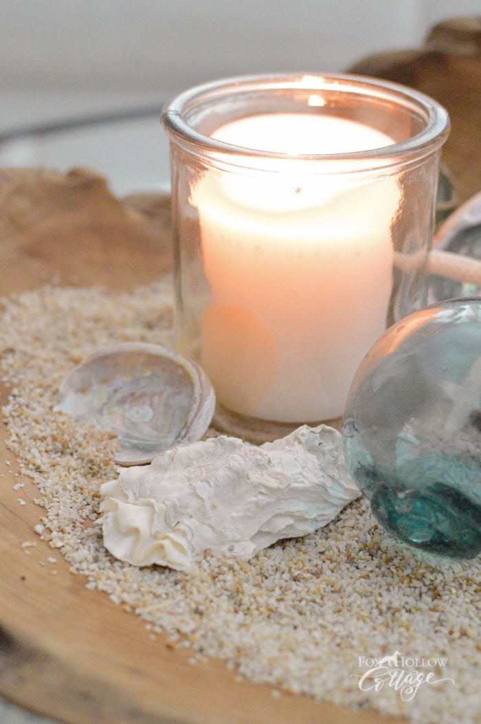 white votive candle in glass holder in bowl with sand and shells