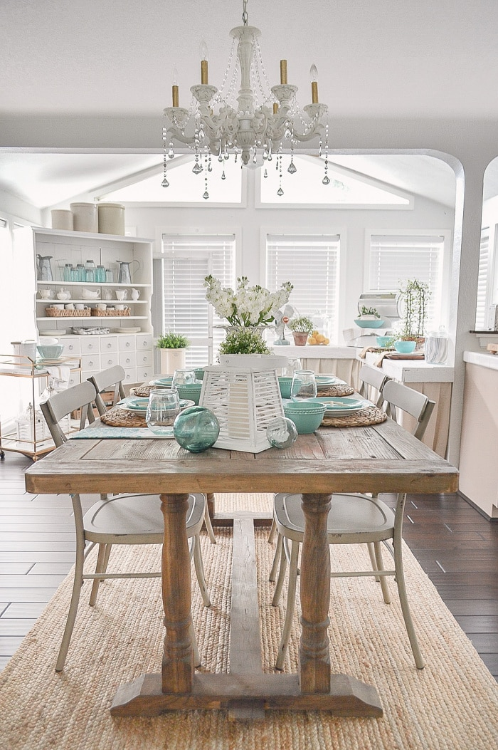 view looking from dining room into kitchen with wood table and all white walls and a few blue accessories