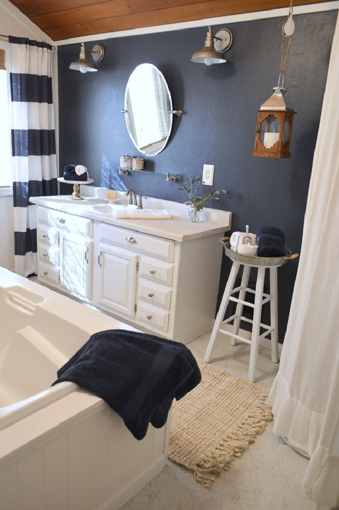bathroom with black wall and white vanity and farmhouse decor