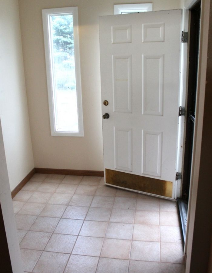 home tour of avid crafter entry way before picture with white walls and white door blank space