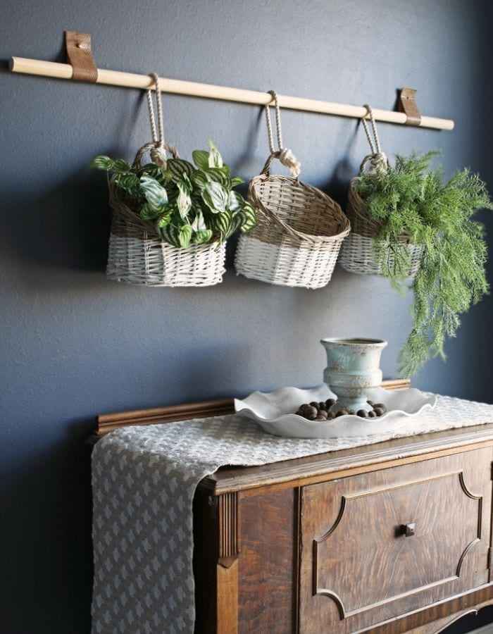 after picture of entryway with a basket hanging wall decor in a dark blue statement wall