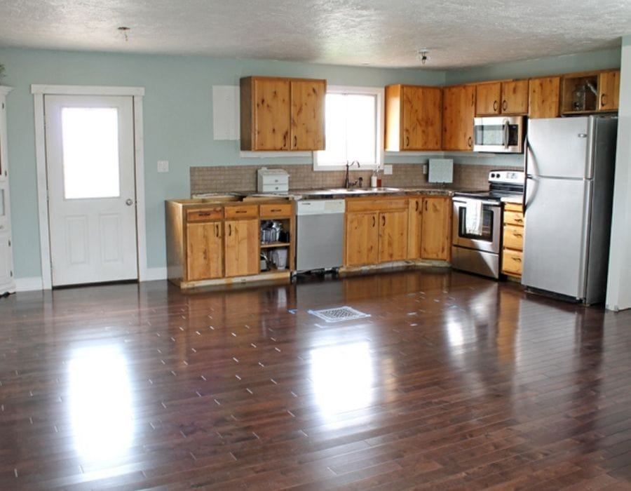 picture of home tour kitchen after DIY makeover transformation with new dark flooring, new backsplash and cabinets