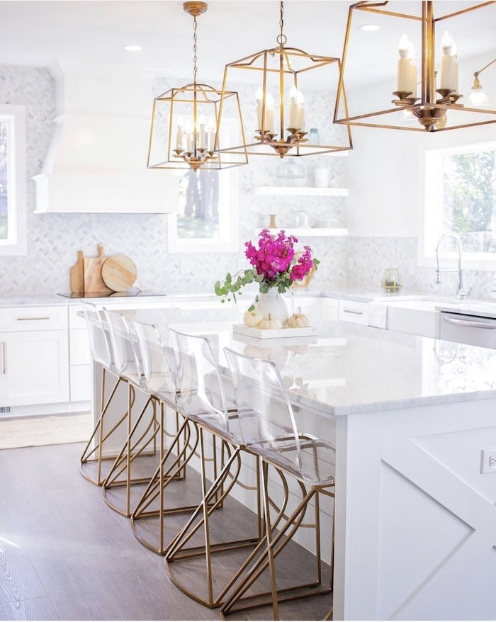 kitchen with white cabinets and brass pendants above island with acrylic and gold bar stools