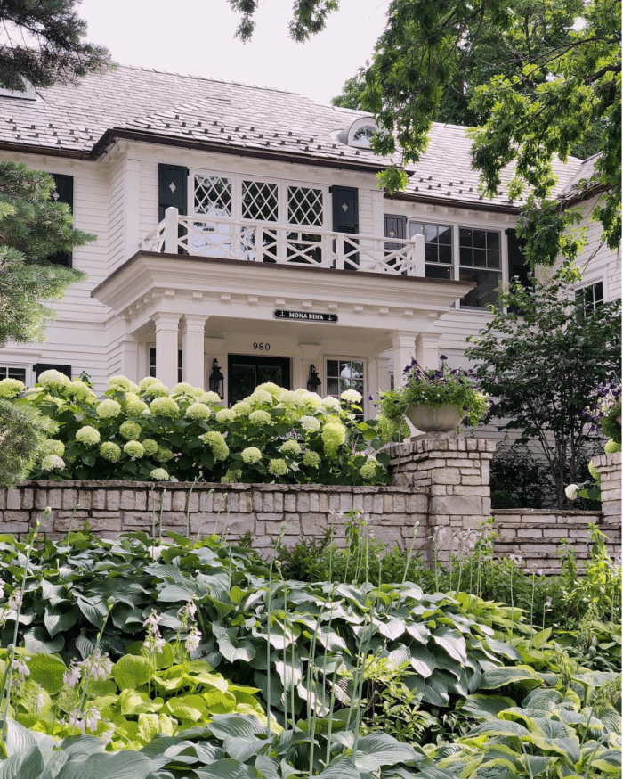 exterior of white home surrounded by lush landscaping