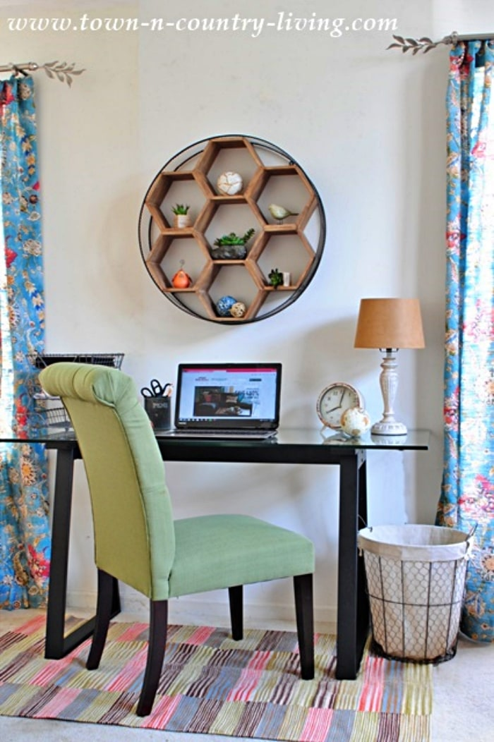 home office desk, wall hanging and a green office chair on a multi colored rug