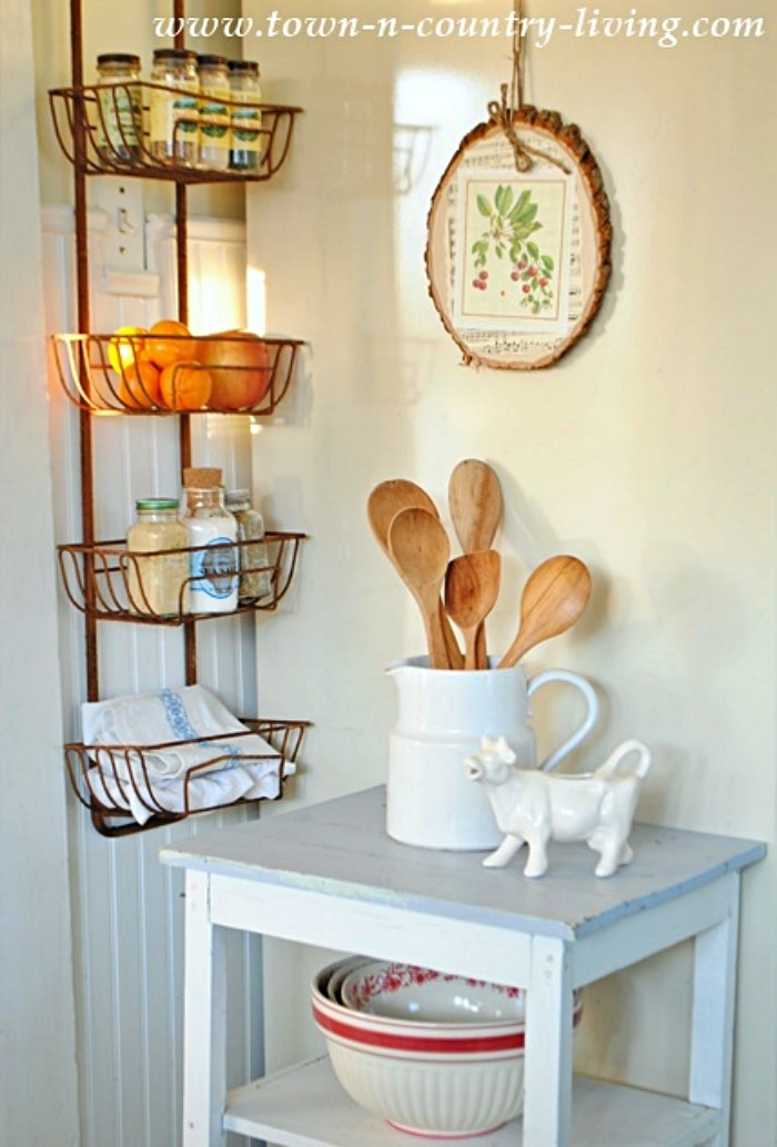 tiered wall basket hanging in a kitchen filled with accessories and food surrounded by decor