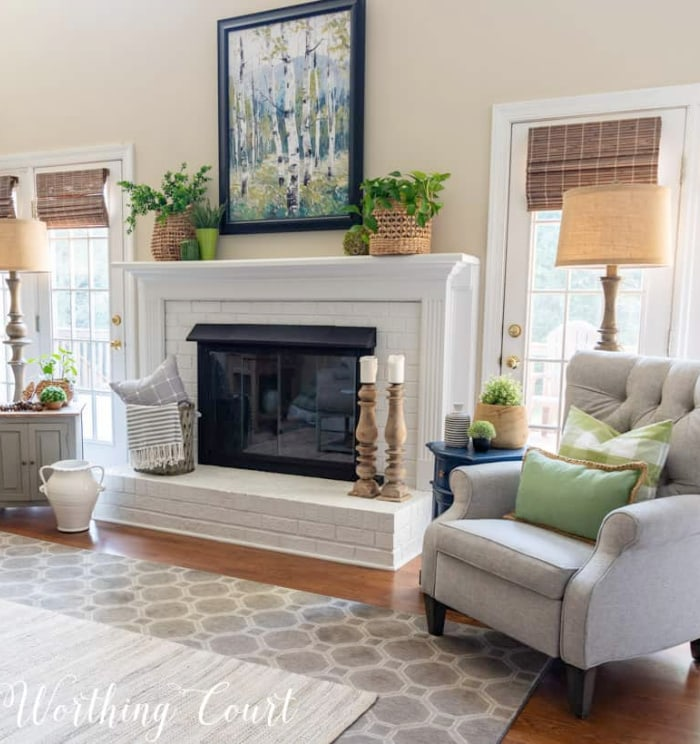gray tufted back chair beside white fireplace with summer decor