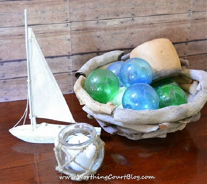 nautical vignette with green and blue glass orbs in a driftwood bowl
