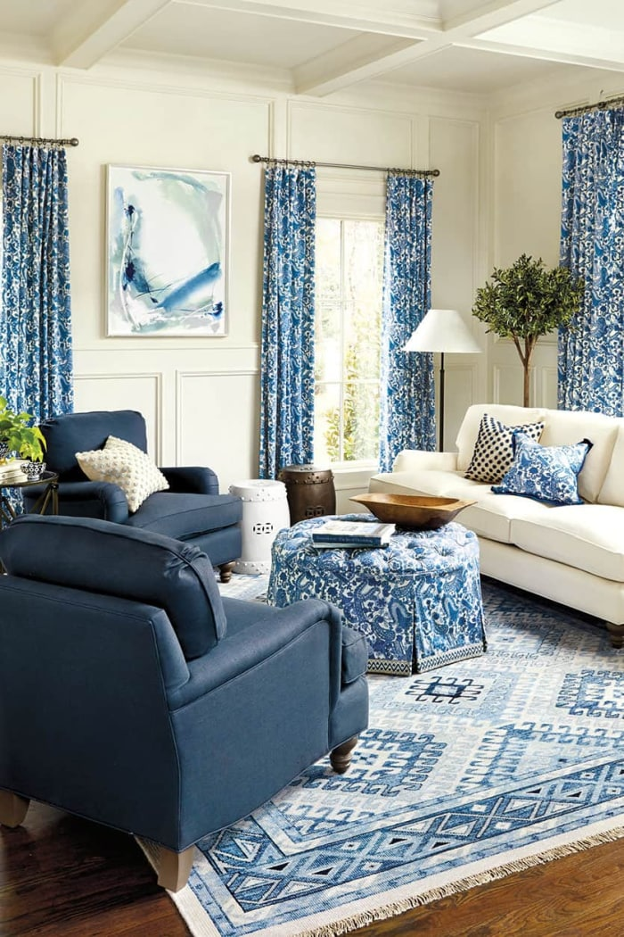 living room with all blue and white decor - blue chairs, blue and white rugs, ottoman and draperies with white walls