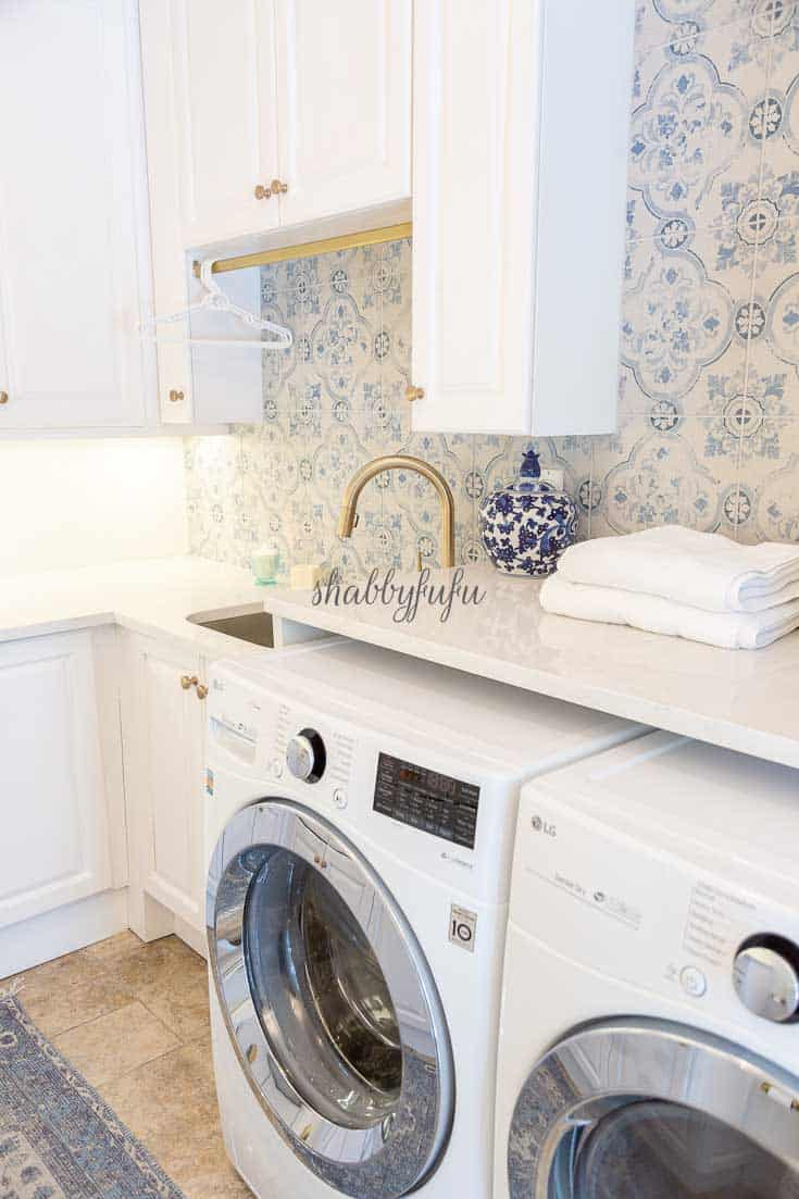 laundry room with white washer, dryer and cabinets with blue and white wallpaper