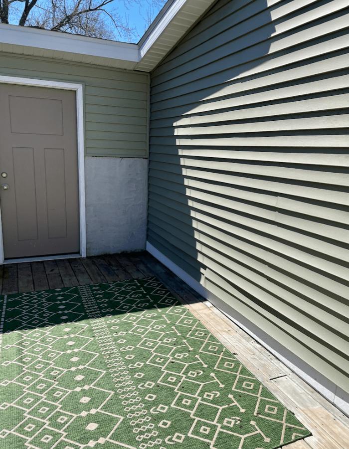 features outdoor deck with outdoor rug in green tones, door, green walls