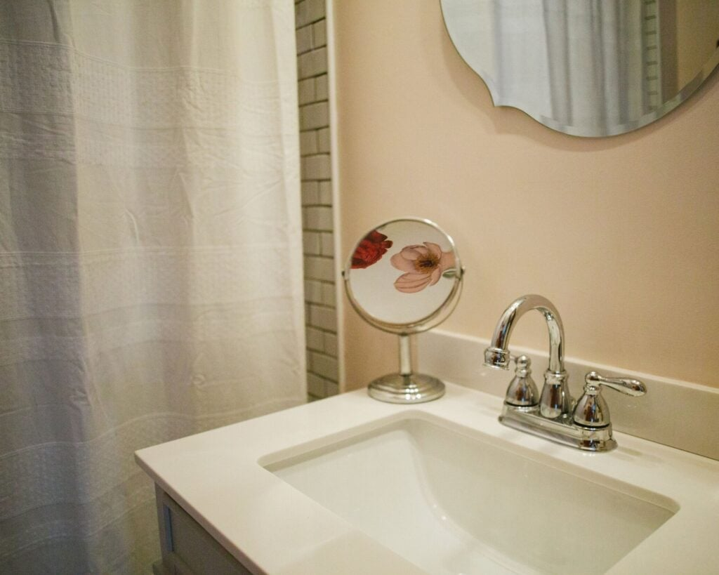 bathroom wall with round mirror, flower painted on the ceiling, pink flowers, white shower curtain