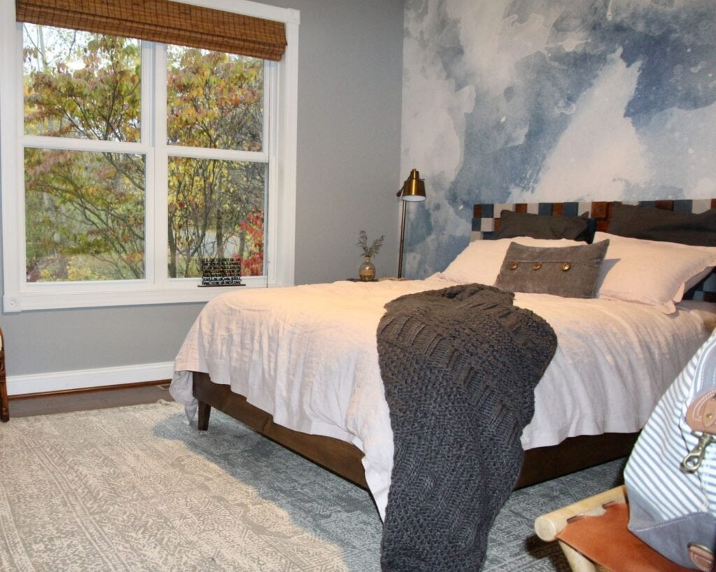 renovated and redecorated bedroom. White bed, accent wall in blue, throw blanket