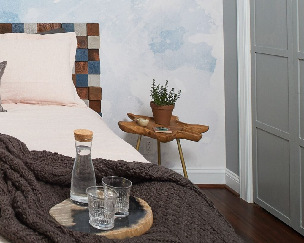 bed with navy throw blanket, water glass and bottle in tray on top of bed