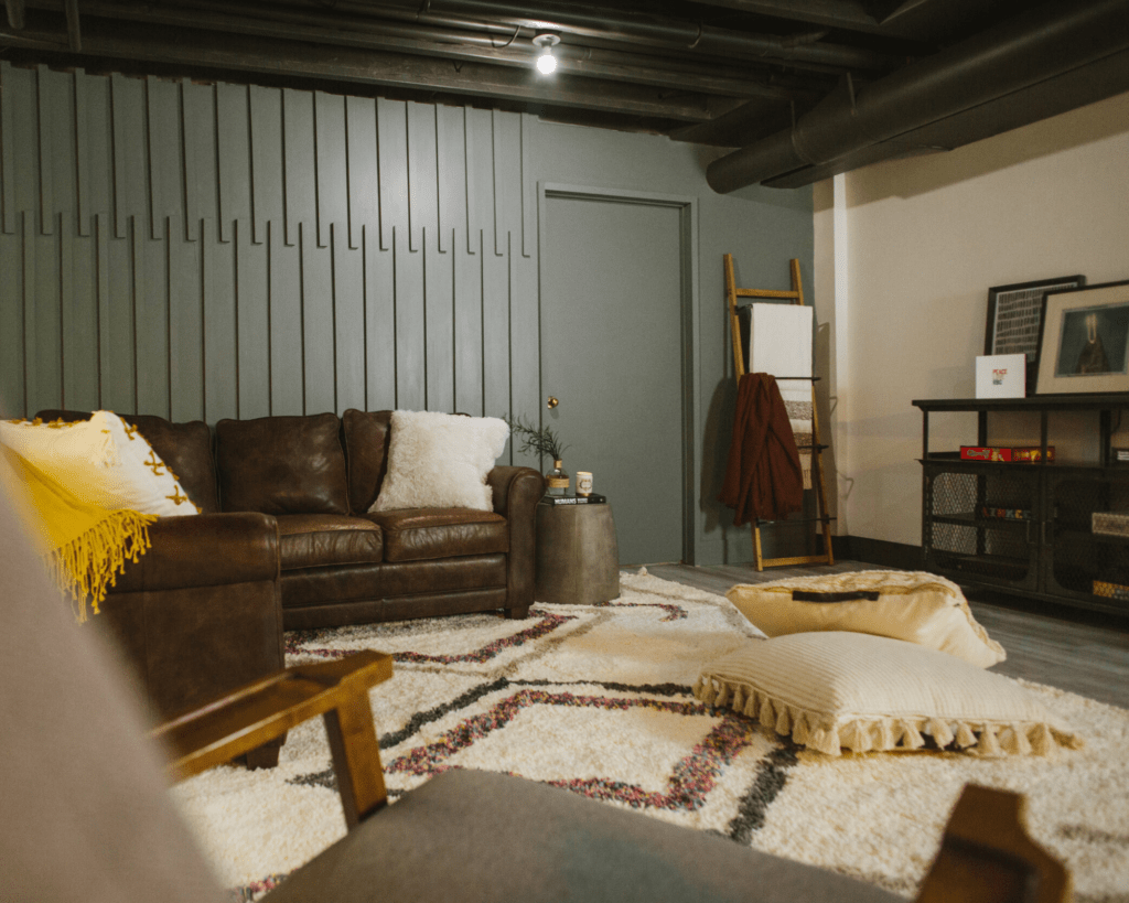 basement renovation makeover, brown couch, mid century style, boho area rugs, dark green accent wall