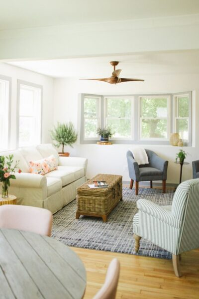 living room featuring sofas, couch, boho styled lamp, white windows and light green walls
