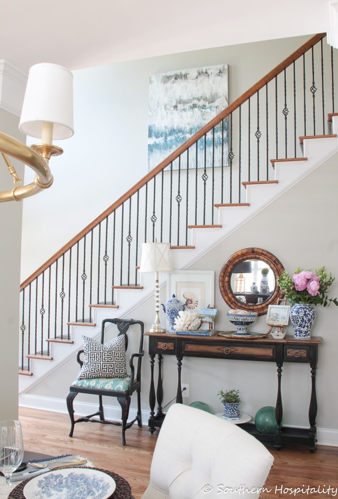 staircase with handrail, large artwork on a wall and a console table beneath the handrail