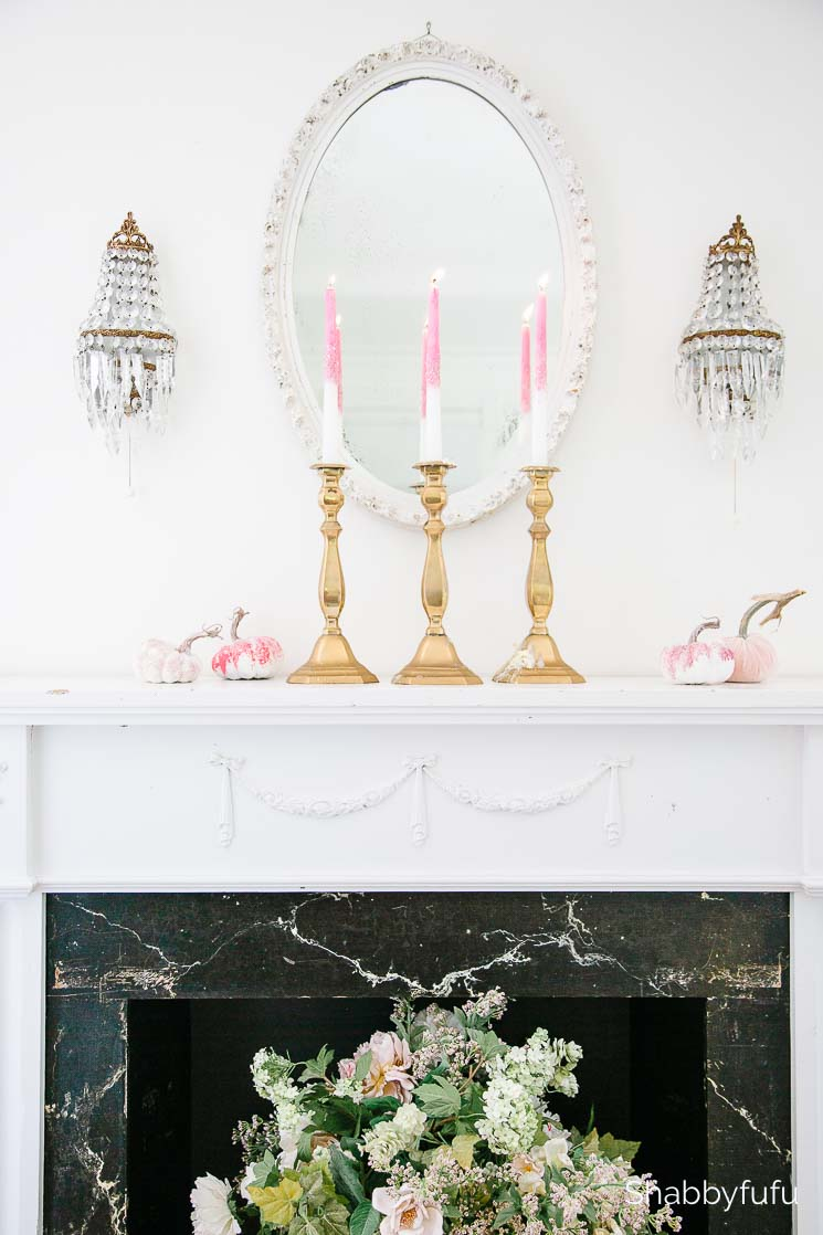 three gold candlesticks with pink and white candles on a white mantel with an oval mirror flanked by crystal sconces above