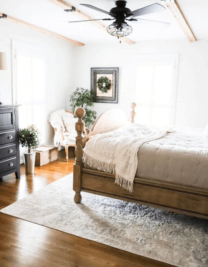 elegant and airy farmhouse bedroom featuring a large bed in creamy hues