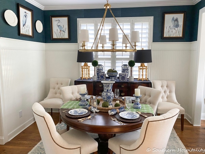 dining room with navy and white walls, round dining table, white chairs, blue and white accessories