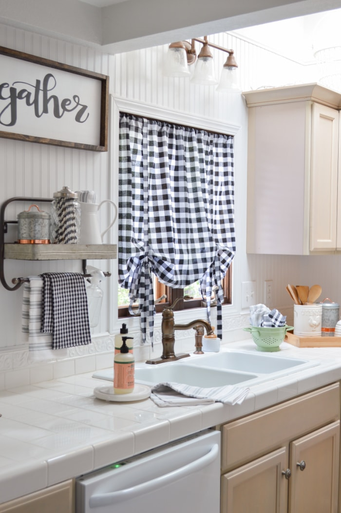 kitchen sink in white cabinets with white counters with a window above with a black and white checked relaxed roman shade