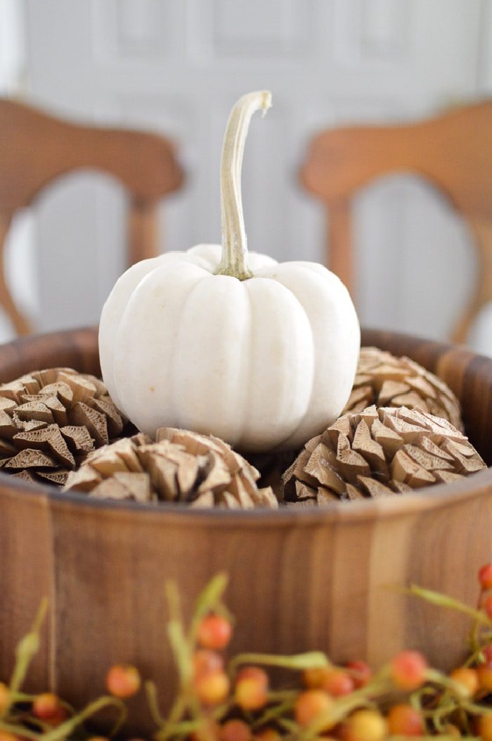 white pumpkin sitting on top of pine cones in a copper bowl