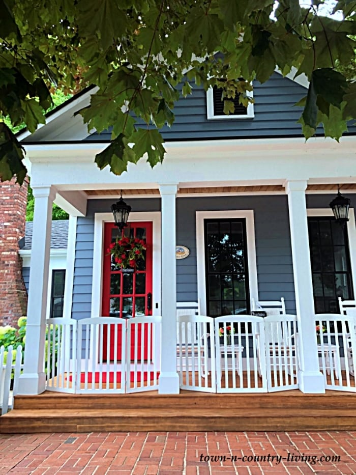 exterior of blue house with a red door and white porch fence